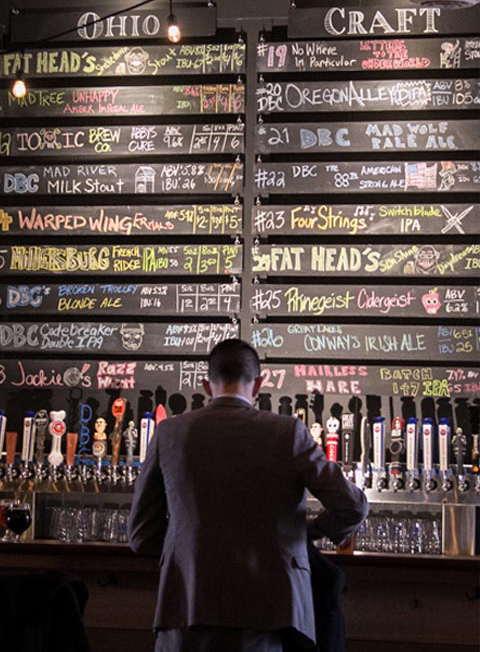 Man in front of beer list at Downtown Dayton location